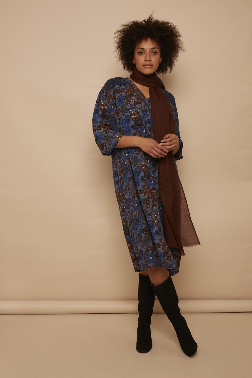 Model trägt Kleid mit Blumen in blau braun kombiniert mit einem braunen Schal von der Modemarke Masai Clothing Company