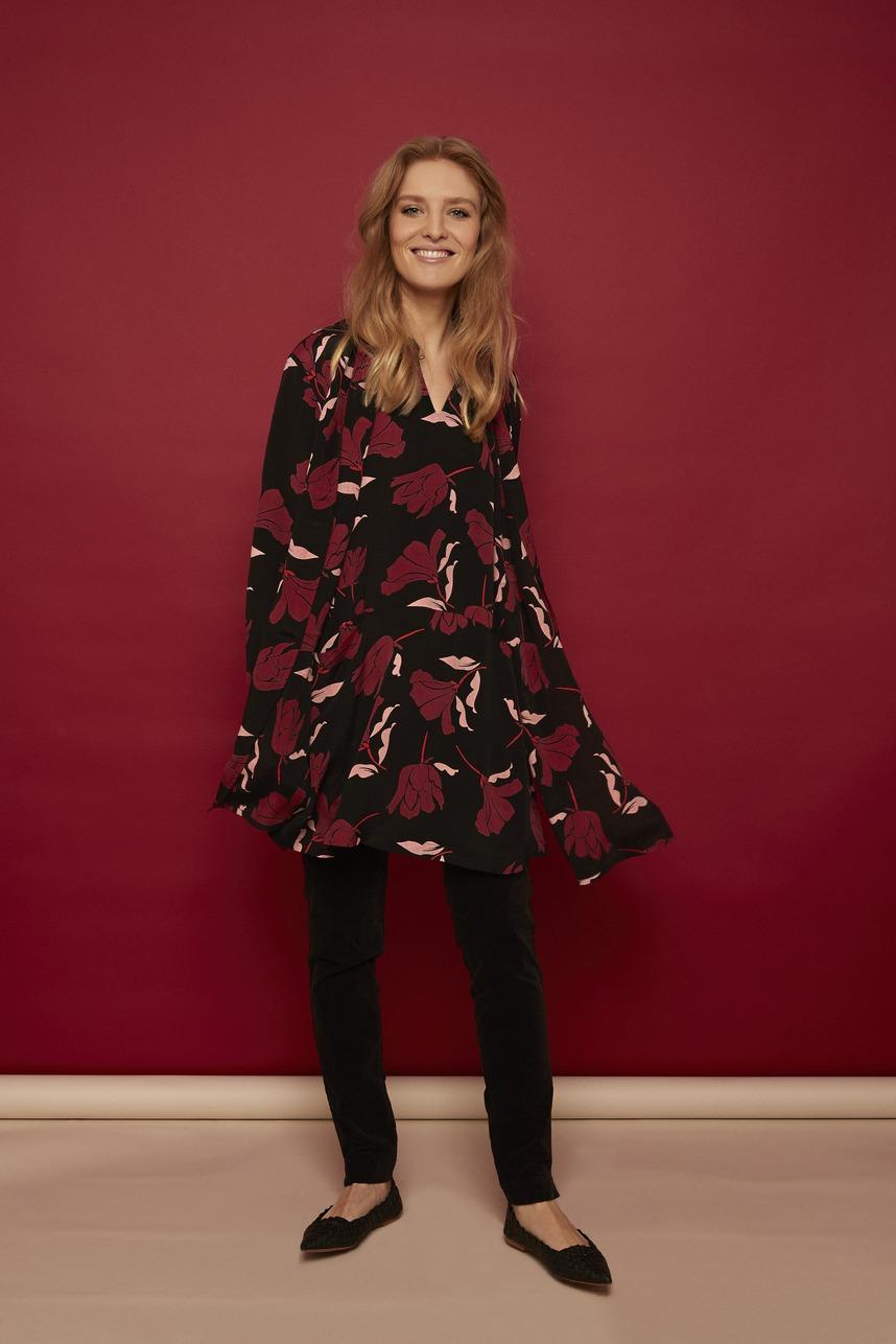 Model trägt Kleid Tunika mit bordeaux rotem Tulpen Muster von der Modemarke Masai Clothing Company