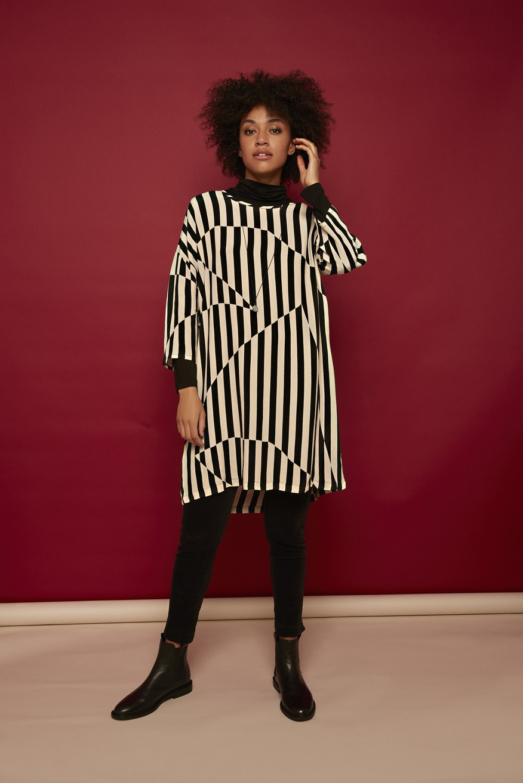 Model trägt Tunika, kurzes Kleid schwarz weiss mit unregelmäßigen Streifen von der Modemarke Masai Clothing Company